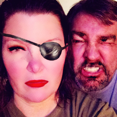 cover of Leslea podcast: Leslea is stoic, with a pirate's eyepatch and intense makeup. Tim menaces over her shoulder like a pirate from days of olde.